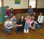 The Youth Group posing with canned goods and the director of the Food Pantry