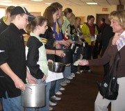 Another member donates her $1 for the \'Souper Bowl of Caring\' at United Church Westside in Westside, Iowa